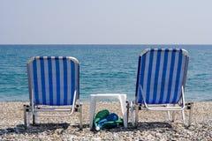 Playa-Sillas que pasan por alto el océano Imagen de archivo