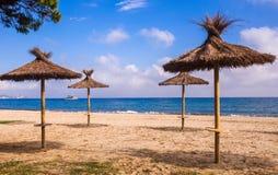 Playa sola, sombrillas de la paja, mar, cielo azul y velocidad turística Foto de archivo
