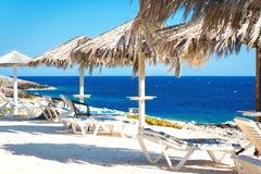 Playa soleada con los sunbeds Foto de archivo libre de regalías