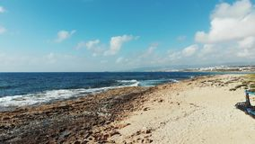 Playa sucia archivada con las botellas y la construcción metálica plásticas Vista aérea de las ondas del mar que golpean la playa metrajes