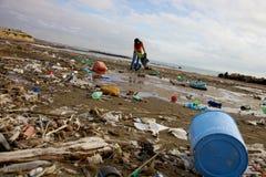 Playa sucia limpia de la mujer terrible del desastre ecológico Foto de archivo libre de regalías