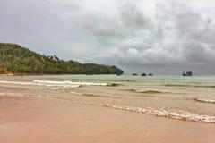 Playa tropical bajo el cielo melancólico Foto de archivo