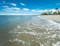 Playa tropical blanca amplia de Sandy con los smallwaves Imagenes de archivo