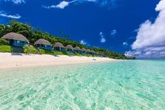 Playa tropical con con las palmeras y los chalets, Polinesia fotos de archivo libres de regalías