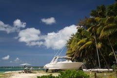 Playa tropical con el barco y las palmas Fotos de archivo