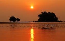 Playa tropical con la isla de las palmeras en la puesta del sol Imagen de archivo
