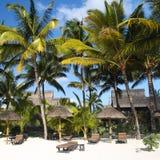 Playa tropical con las palmeras delante de un hotel Imágenes de archivo libres de regalías
