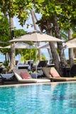 Playa tropical hermosa, palmera, agua de mar, paraguas y sunbed en un día soleado tailandia Imagen de archivo
