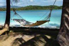 Playa tropical perfecta con las palmeras y la hamaca imagen de archivo