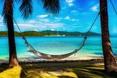 Playa tropical perfecta con las palmeras y la hamaca imagen de archivo libre de regalías