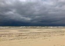 Playa vacía con las nubes de lluvia y las pistas oscuras bajas de la rueda en la arena, los Países Bajos fotografía de archivo libre de regalías
