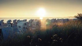 Playa vacía con las sillas de playa en la salida del sol Foto de archivo libre de regalías