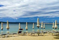 Playa vacía con las sombrillas cerradas, Croacia, weath tempestuoso del mar Fotos de archivo