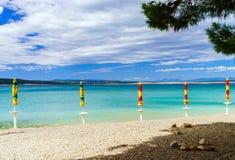 Playa vacía con las sombrillas cerradas, Croacia, weath tempestuoso del mar Fotografía de archivo libre de regalías