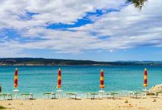 Playa vacía con las sombrillas cerradas, Croacia, weath tempestuoso del mar Fotos de archivo libres de regalías