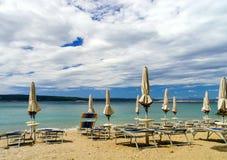 Playa vacía con las sombrillas cerradas, Croacia, weath tempestuoso del mar Imagen de archivo