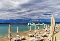 Playa vacía con las sombrillas cerradas, Croacia, weath tempestuoso del mar Imagenes de archivo