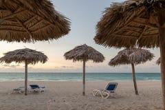 Playa vacía con los deckchairs y los paraguas de las hojas de palma Concepto de las vacaciones foto de archivo