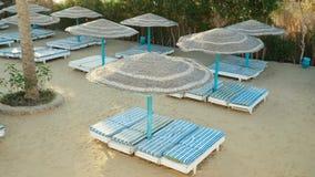 Playa vacía con los paraguas, cama del sol almacen de metraje de vídeo