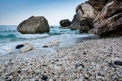 Playa vacía de Cala Gonone en Cerdeña con las rocas y las ondas en un o imagenes de archivo