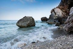 Playa vacía de Cala Gonone en Cerdeña con las rocas y las ondas en un o imagen de archivo