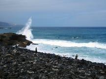 Playa volcánica negra típica en Tenerife con el mar azul profundo y una onda que se rompe sobre rocas con las piedras apiladas foto de archivo libre de regalías