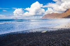 Playa volc?nica de Famara con una tabla hawaiana que espera una onda fotos de archivo libres de regalías