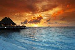 Playa y casas tropicales en puesta del sol Foto de archivo libre de regalías