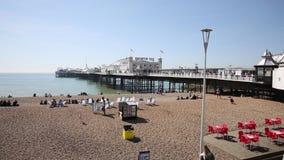 Playa y embarcadero de Brighton con la gente en tiempo hermoso