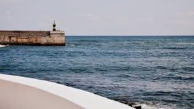 Playa y faro españoles en el pueblo de Comillas, Cantabria Foto de archivo libre de regalías