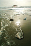 Playa y resaca del Océano Pacífico con las ondas en la arena y una isla Imagen de archivo libre de regalías