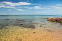 Playa y roca en día claro Imagenes de archivo