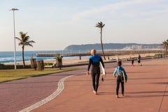 Playas de Durban del hijo del papá que practican surf Fotos de archivo libres de regalías