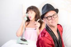 Playboy med kvinnan på telefonen och röka i bakgrund royaltyfri bild