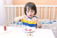 可爱的小男孩做了棒棒糖playdough和牙签 库存照片