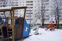 Playdround vazio das crianças da neve com bancos, corrediça e torniquete Imagem de Stock Royalty Free
