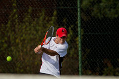Player Backhand Tennis Teenager. Teenage male player focused hitting the ball on his back hand against his opponent at high schools tennis tournament Stock Images
