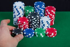 The player bets; puts chips in pot. The player bets; puts chips in the pot, the stack of chips on the green table Royalty Free Stock Image