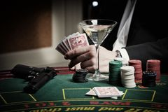 The player in the casino. Poker, gun, card game royalty free stock photography