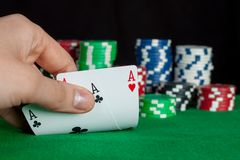 Player checks his hand, two aces in, focus on card Stock Photography