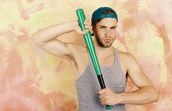 Player with confident face plays baseball. Sports and baseball training concept. Guy in grey tank top. Holds bright green bat. Man in cyan green cap on pink Stock Photography
