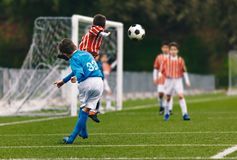 Player Cross a Football Soccer Ball. Boys Playing Football Game on Stadium Pitch. Kid Junior Soccer League Match. School Sports Competition stock photography
