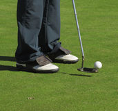 Player, golf club and ball. Lady legs with golf shoes while putting the ball on a training putting green Royalty Free Stock Images