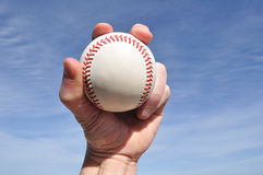 Player Gripping a New Baseball. Against a Blue Sky Stock Image
