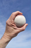 Player Gripping a New Baseball. Against a Blue Sky Royalty Free Stock Images