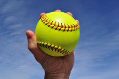 Player Gripping a Yellow Softball. Against a Blue Sky Royalty Free Stock Photo