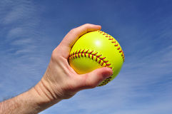 Player Gripping a Yellow Softball. Against a Blue Sky Stock Photo