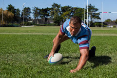 Player holding ball while playing rugby on field. During sunny day royalty free stock image