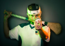 Player Holding Hurling Ball. A hurling player holds a ball in front of his face holding the stick on his shoulders. shallow depth of field. green and orange Stock Photography