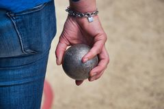 A player holds in hand a boule for petanque royalty free stock photo